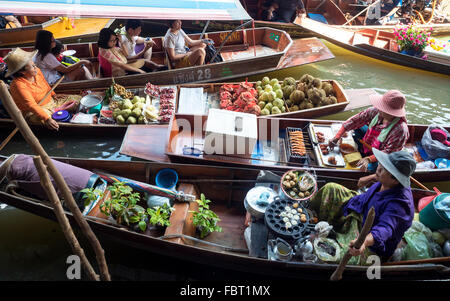 Floating Market with boats and sellers on a canal or Khlong, Damnoen Saduak, Ratchaburi Province, Thailand - Stock Photo