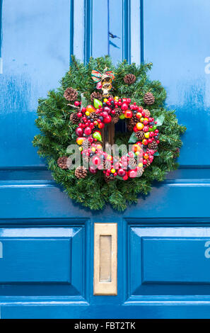 Christmas wreath on blue front door hanging - Stock Photo