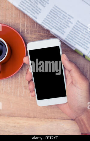 Person using smart phone by coffee and newspaper on table - Stock Photo