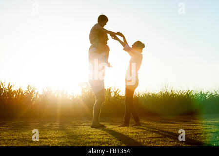 Family with little boy basking in glow of later afternoon sun - Stock Photo