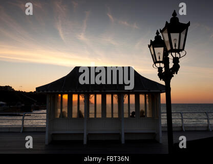 Four people sitting in one of the Victorian ornamental shelters on Cromer Pier, Norfolk, England, UK watching the sunset