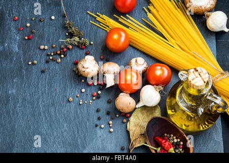 Italian meal ingredients with pasta,spices,tomatoes,olive oil,mushrooms - Stock Photo