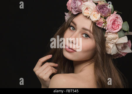 Portrait of a lovely woman with wreath from flowers on head posing over black background - Stock Photo