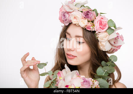 Beauty portrait of attractive tender young female in rose wreath with bouquette of flowers isolated over white background - Stock Photo