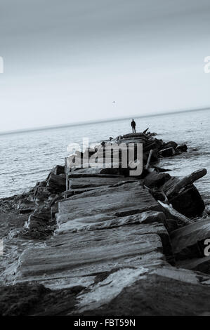 Lone figure of man on jetty overlooking lake.  Cool toned image in black and white. - Stock Photo
