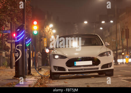 Tesla luxury electric car at a charging point in Kensington, London - Stock Photo