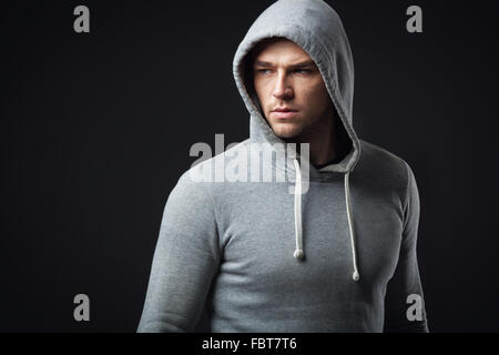 Studio portrait of cool looking young guy in sportswear. - Stock Photo