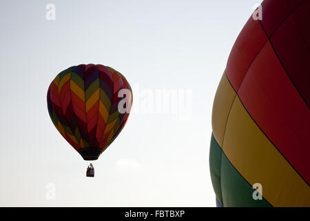 Hot air balloon rising and passing by a second balloon still on the ground - Stock Photo