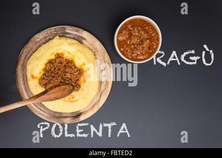 A dish of Polenta with bolognese soup (aka Ragu) standing on a black-board. Ragu and polenta on the blackboard - Stock Photo