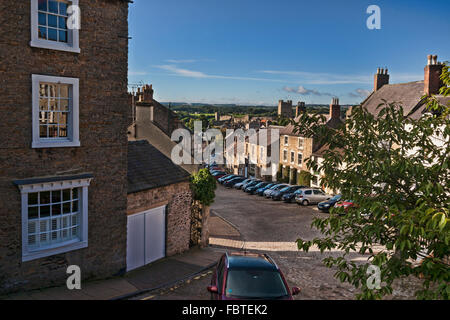 Looking down cobbled street to Richmond Castle, North Yorkshire, England - Stock Photo