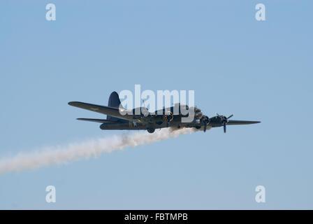 Boeing B-17 flies with smoke trail - Stock Photo