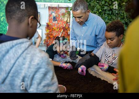 U.S President Barack Obama plants vegetable seeds with students during a Martin Luther King, Jr. Day of Service - Stock Photo