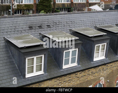 Dirty solar panels on dormer window rooftops, Brentford, London, UK. In need of cleaning. - Stock Photo