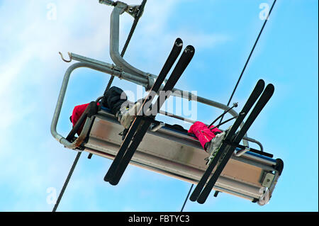 Skiers couple on a ski lift. View from below - Stock Photo