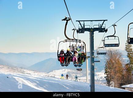 Skiers on a ski lift in Bukovel. Bukovel is the most popular ski resort in Ukraine. - Stock Photo