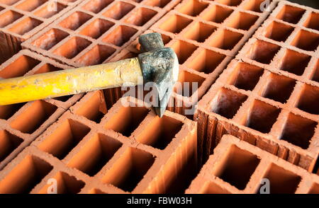 Hollow brick with hammer - Stock Photo