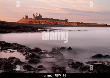 Evening light over the 14th Century fortification - Dunstanburgh Castle sitting on the Northumberland coast - Stock Photo