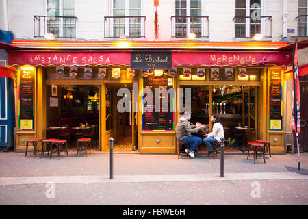 Sidewalk cafe street scene with people dining from the Latin Quarter in Paris France - Stock Photo