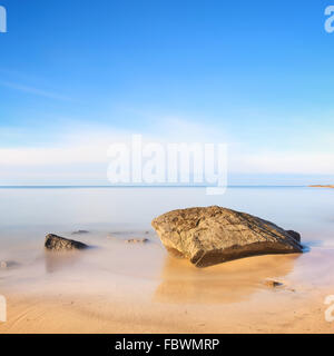 A flat rock on a golden sand beach and blue ocean. Long exposure photography. - Stock Photo