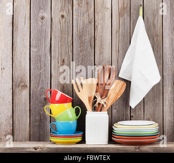 Kitchen utensils on shelf against rustic wooden wall - Stock Photo