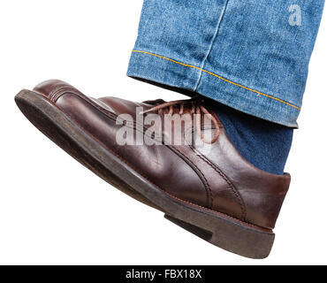 side view of male left leg in jeans and brown shoe takes a step isolated on white background - Stock Photo