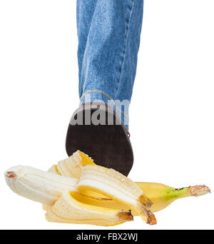 male left foot in jeans and brown shoe stepping on banana isolated on white background - Stock Photo