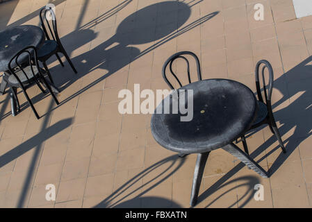 Alfresco dining.  Outdoor black metal table and chairs casting deep shadows in the early morning light.  Bomdila, - Stock Photo