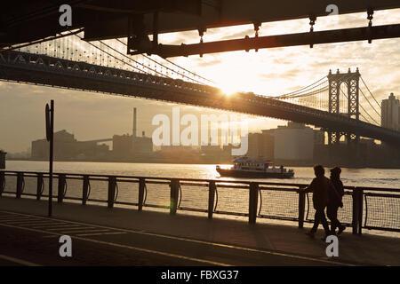 Two women walk north on the East River Esplanade as the sun rises over the Manhattan Bridge New York City - Stock Photo