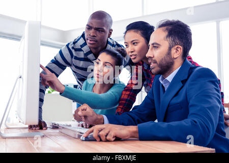 Businesswoman explaining colleagues over computer - Stock Photo