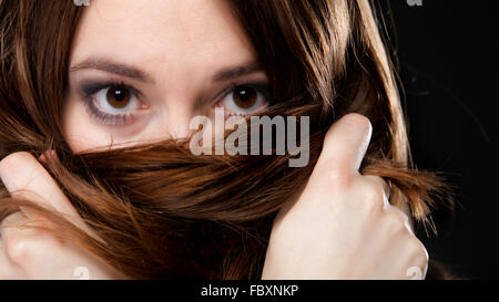 Closeup woman covers the face by long brown hairs