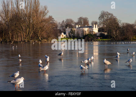 A view over the frozen lake in Regents Park, London.  The Holme mansion can be seen in the distance. - Stock Photo