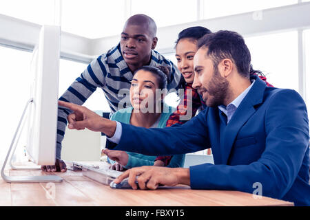 Businessman explaining colleagues over computer - Stock Photo
