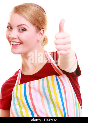 Happy housewife in kitchen apron showing thump up hand sign - Stock Photo