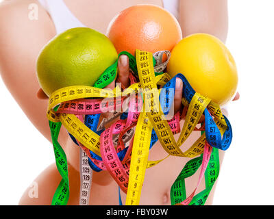 Sporty fit woman with measure tapes fruit. Time for diet slimming. - Stock Photo