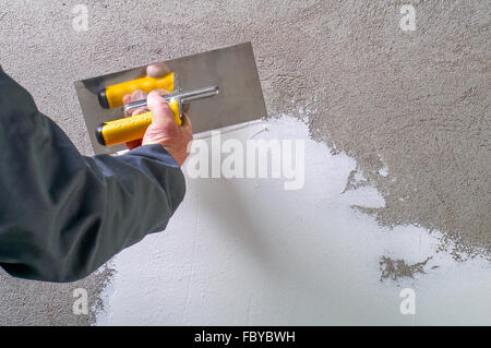 Construction worker - plastering and smoothing concrete wall with white cement by a steel trowel - spatula aligns - Stock Photo
