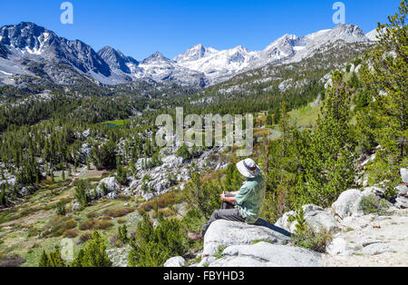 Hiker relaxes at overlook with view of Little Lakes Valley in Rock Creek Canyon in the Eastern Sierra in Northern - Stock Photo