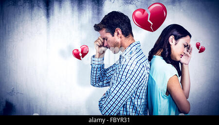 Composite image of depressed couple standing back to back - Stock Photo