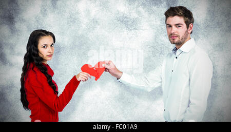 Composite image of portrait of couple holding red cracked heart shape - Stock Photo