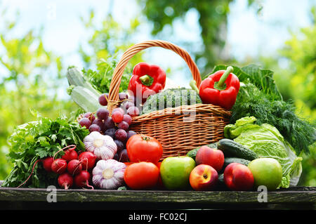 Fresh organic vegetables in wicker basket in the garden. - Stock Photo