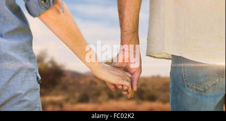 Composite image of couple holding hands in park - Stock Photo