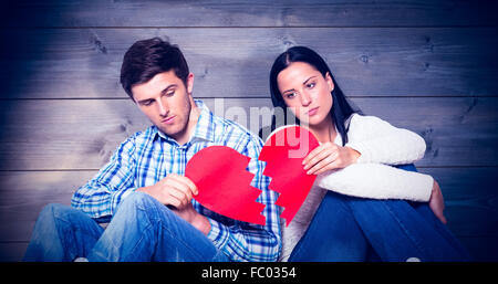 Composite image of young couple sitting on floor with broken heart - Stock Photo