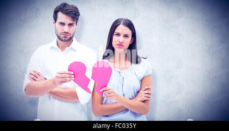 Composite image of upset couple holding two halves of broken heart - Stock Photo