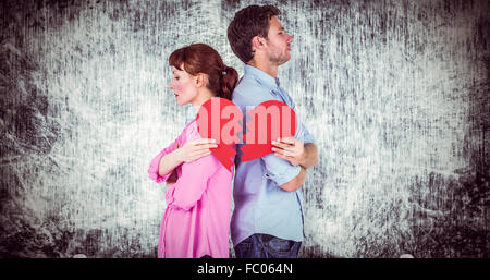 Composite image of couple holding a broken heart - Stock Photo