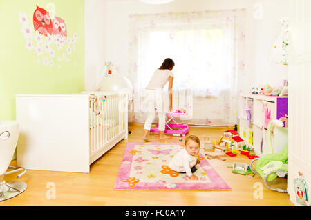 Young mother with baby in childrens room - Stock Photo