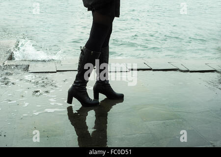 a woman in boots walking along the quay - Stock Photo