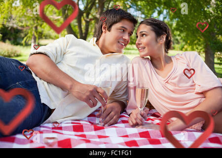 Composite image of two friends looking at each other while having a picnic - Stock Photo