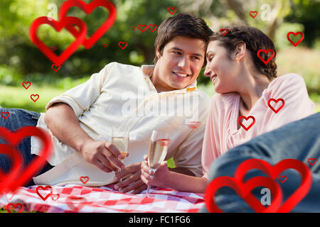 Composite image of man smiling as he looks at his friend during a picnic - Stock Photo