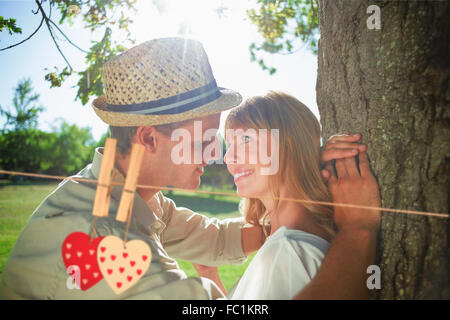 Composite image of cute smiling couple leaning against tree in the park - Stock Photo