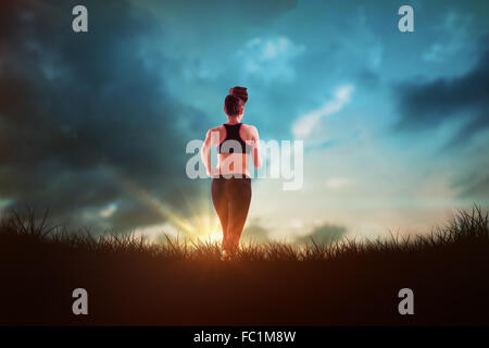 Composite image of fit brunette jogging away from camera - Stock Photo