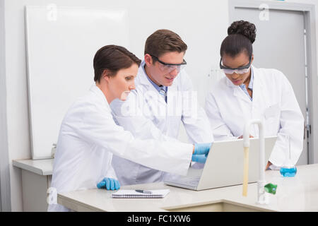 Concentrated scientists working together with laptop - Stock Photo